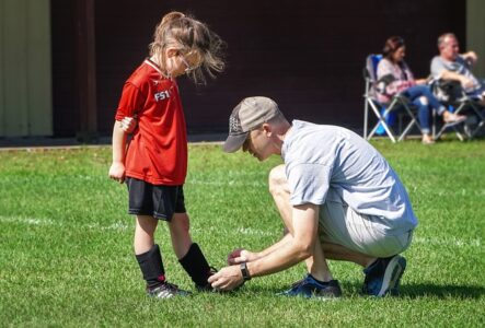 A dad tying his daughter's shoe lace