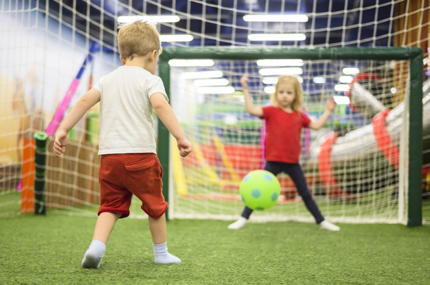 soccer questions and answers - A young boy and a girl playing soccer