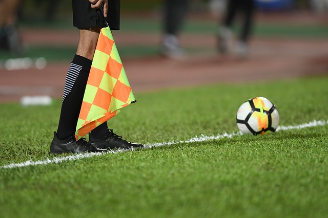 A soccer linesman holding the flag