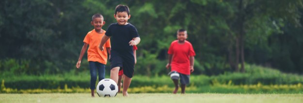 A Boy Running After A Soccer Ball