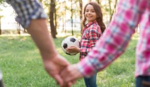 A Girl Enjoying Soccer With Her Parents