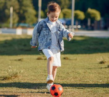 A Little Child Kicking A Soccer Ball