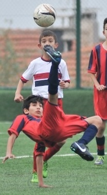 A boy doing the bicycle kick