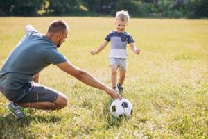 Father with son playing soccer at the field