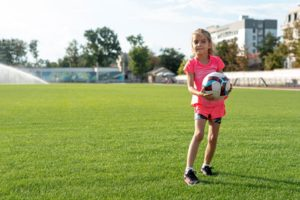 A girl playing with soccer ball