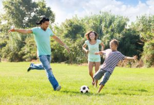 Middle-aged couple with son playing with soccer ball at summer park