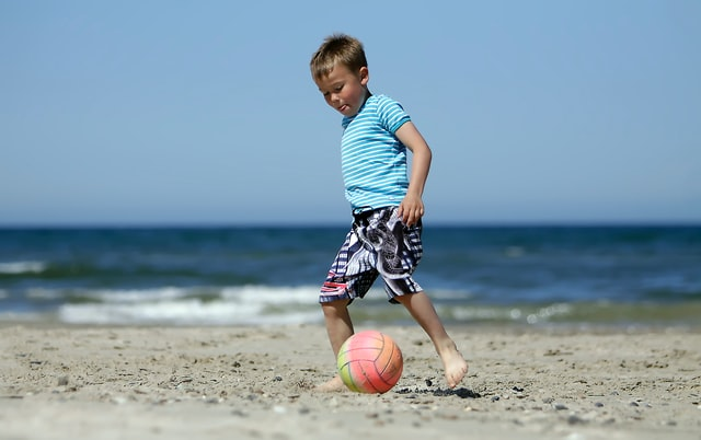 A boy playing soccer on the beach