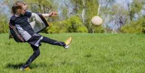 How To Kick A Soccer Ball - A girl kicking a soccer ball