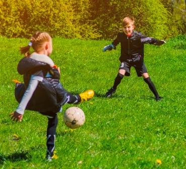 A girl and a boy play with a soccer ball