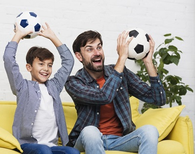 How To Teach Your Child To Play Soccer - father and son watching soccer game
