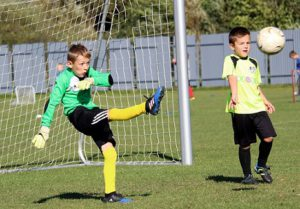 A Boy In Full Goalie Gear Kicking The Soccer Ball