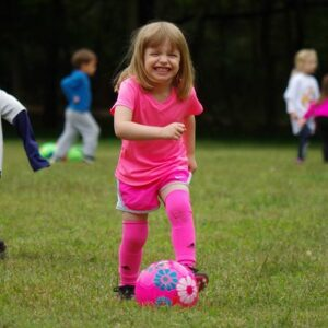 A happy girl playing soccer