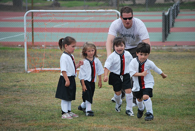 Coach directing girls soccer players during training