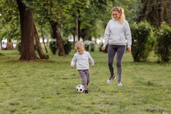 Mother and kid playing soccer