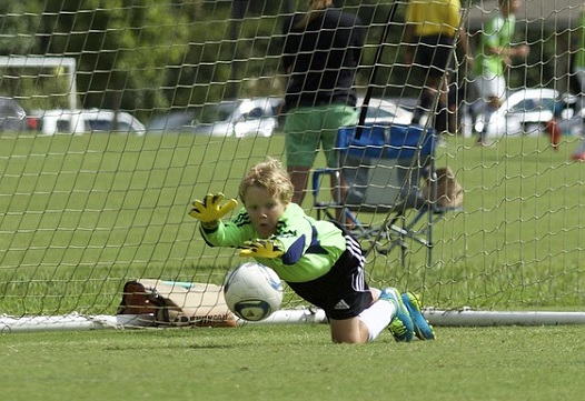 A goalkeeper makes a dive for the ball